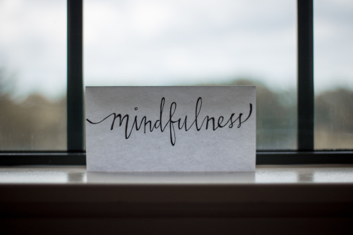 A piece of paper in front of a window with the word mindfulness handwritten on it.