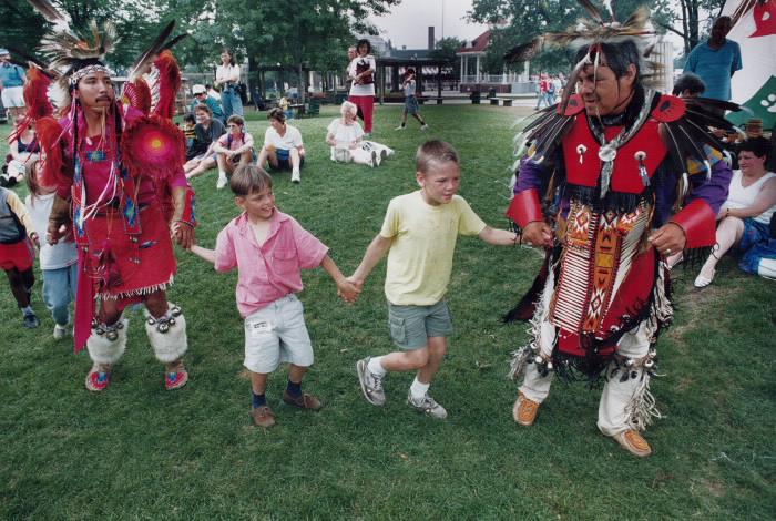 Deux hommes se tenant la main avec deux enfants dans le parc