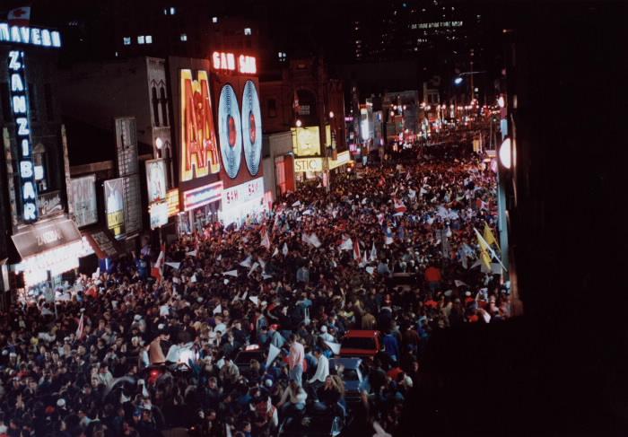 Rue pleine de gens la nuit avec un panneau lumineux de magasin de disques