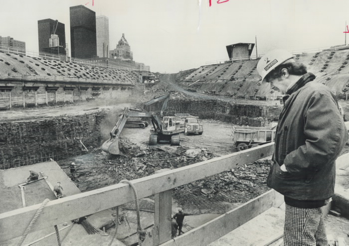 Construction worker looking down into excavated area