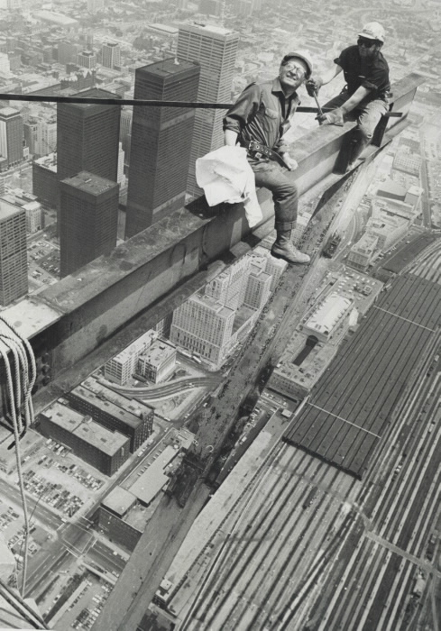Two workers suspended high in air on beam