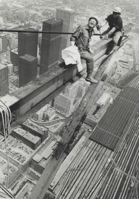 Deux travailleurs suspendus haut dans les airs sur une poutre