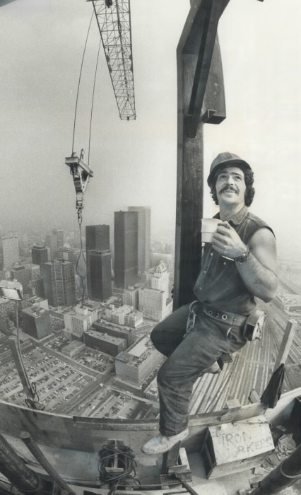 Un ouvrier du bâtiment tenant une tasse et perché en hauteur pendant un projet de construction