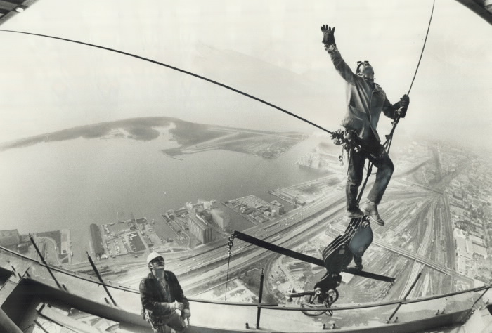 Workers secured by wired stands on a part of a winch high above Toronto