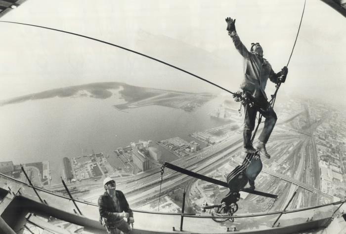 Travailleurs sécurisés par des supports câblés sur une partie d'un treuil au-dessus de Toronto