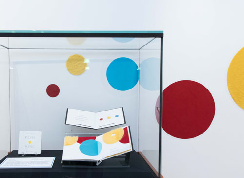 Exhibit case with three books with colourful dots in the books and behind the exhibit case on the wall