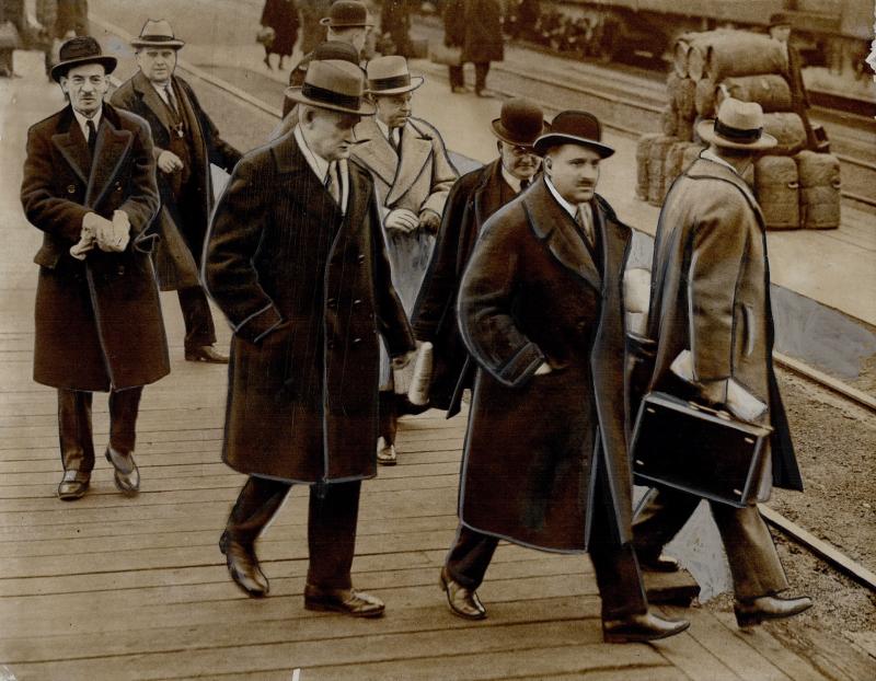 Men in formal attire walking in train station