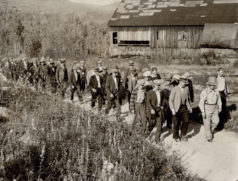 Men marching in grassland in working clothes