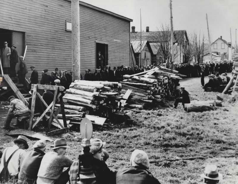 Desolate spot with buildings of men lined up and large piles of wood
