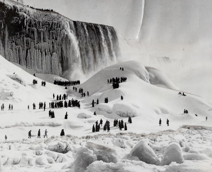 Crowds gather on a snowy landscape with waterfall in background