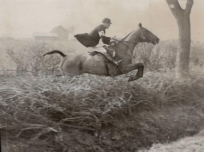 Photo of man riding hours jumping over brush with farm in distant background
