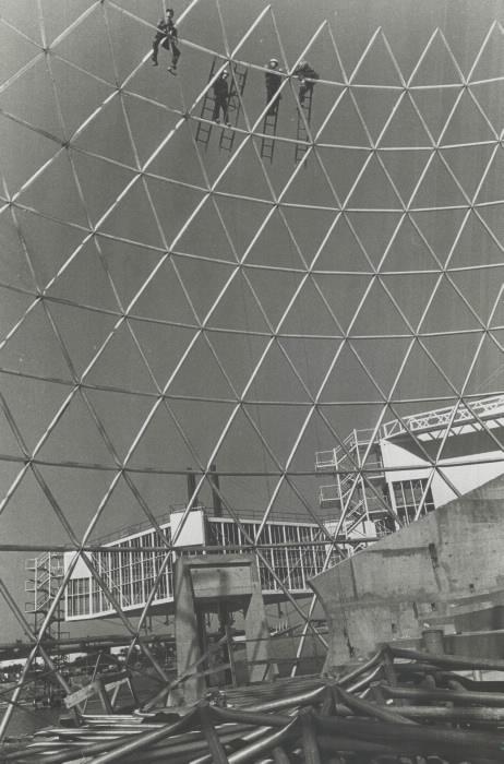 Structure de la grande sphère en construction avec des travailleurs suspendus à des échelles