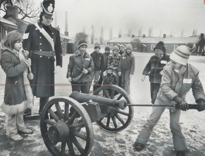 Enfants chargeant un canon historique