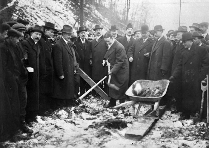 Des hommes se rassemblent autour de quelqu'un qui creuse un trou