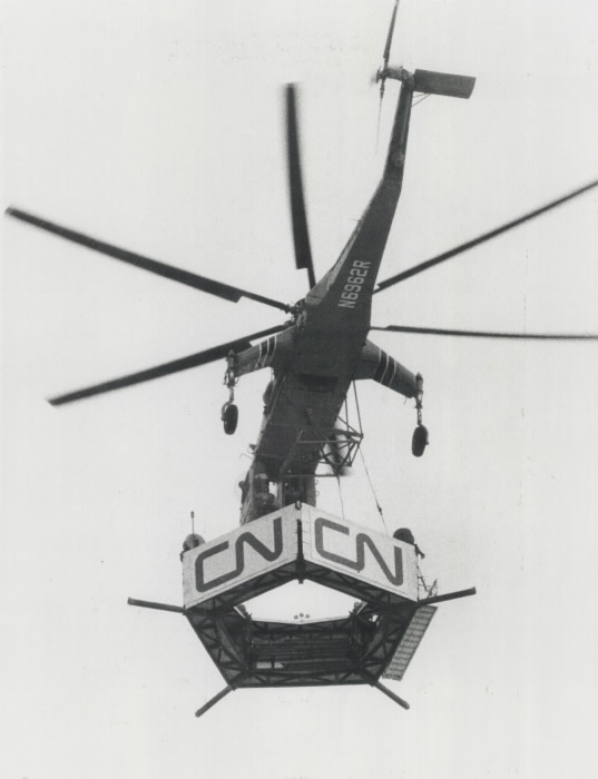 Helicopter hauling a piece of tower with the letters C and N