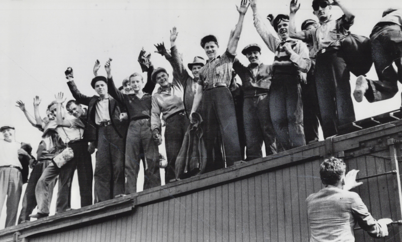 Vintage photo of many men in working clothes waving on top of train