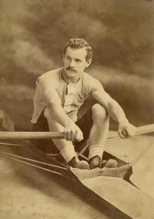 Man posing in vintage row boat