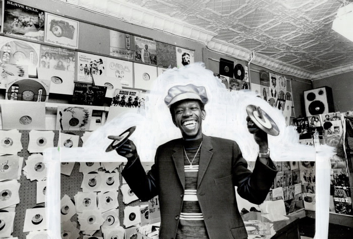 Man holding records on fingers in a record shop