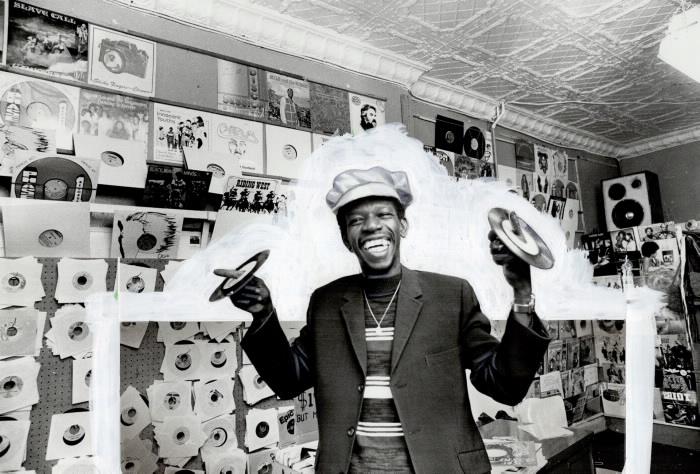 Homme faisant reposer des disques sur ses doigts dans un magasin de disques