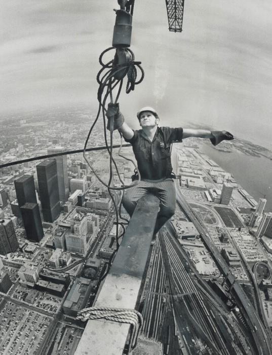 Un ouvrier du bâtiment suspendu dans les airs sur une poutre lançant des cordes