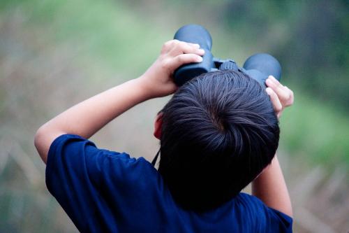 Rearview of child's head while peering through binoculars