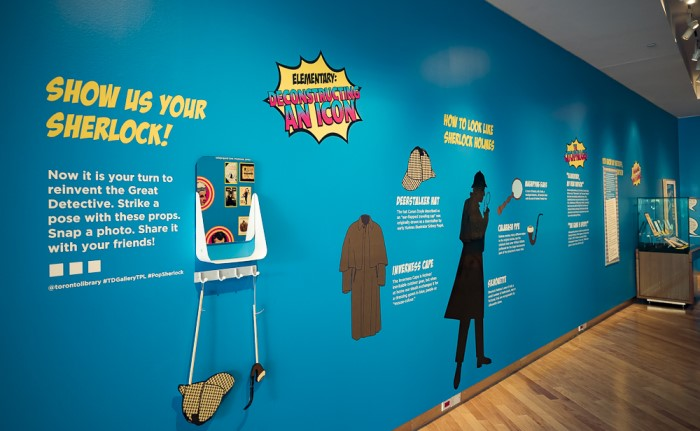 "Interior of Pop Sherlock exhibit in gallery. Text on wall invites visitors to ""Show Us Your Sherlock"" and selfie props are displayed."