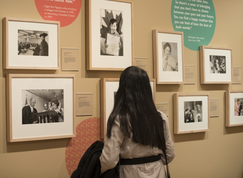 A woman looks at a wall of framed black and white photographs of people of all ages attending citizenship ceremonies.