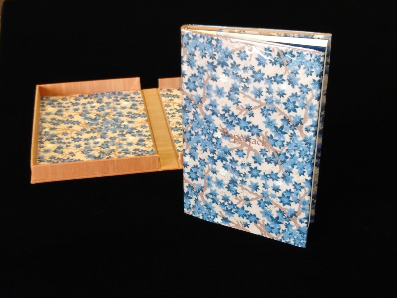 A book covered in Japanese paper alongside an open clamshell box lined with the same paper.