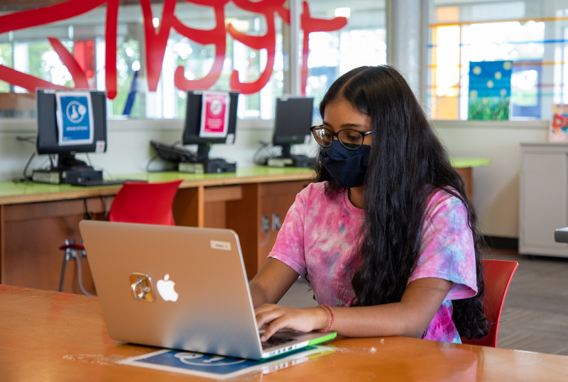 Teen using a laptop wearing a mask