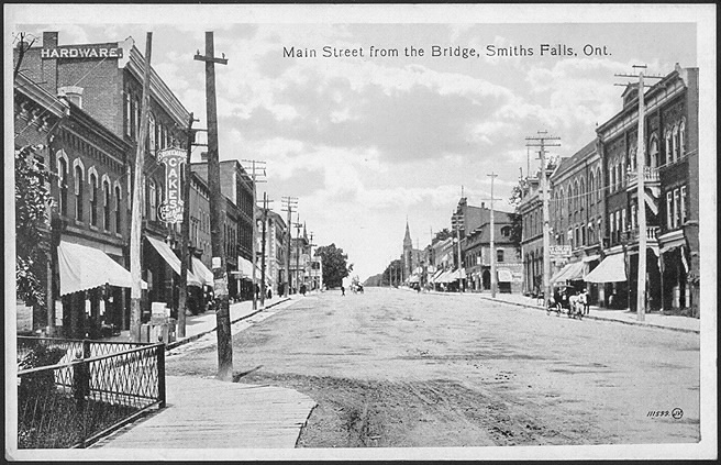 Main street of small town with businesses and a horse and buggy.