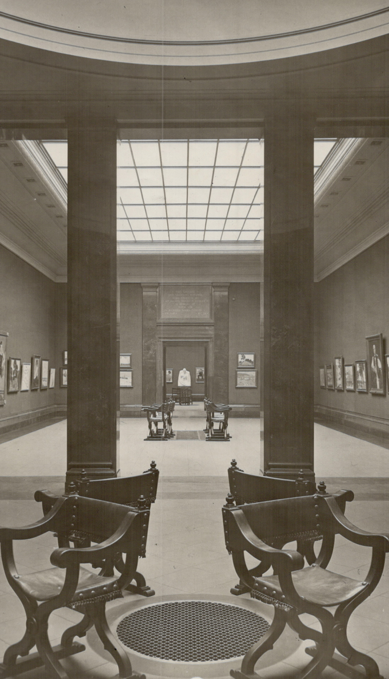 Vintage photograph of large interior exhibit space with paintings on wall and chairs in middle of room