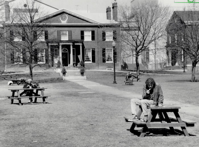 Photo of picnic table with people eating in a park with large brick building in background
