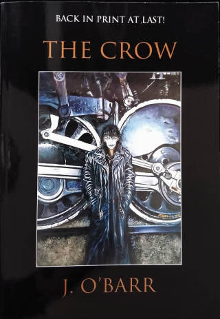 Book cover of The Crow with illustration of person in trench coat with white face in front of large industrial wheels