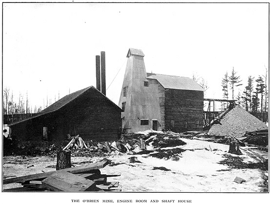 View of two wood buildings with lumber nearby and subtitle The O'Brien Mine Engine Room and Shaft House