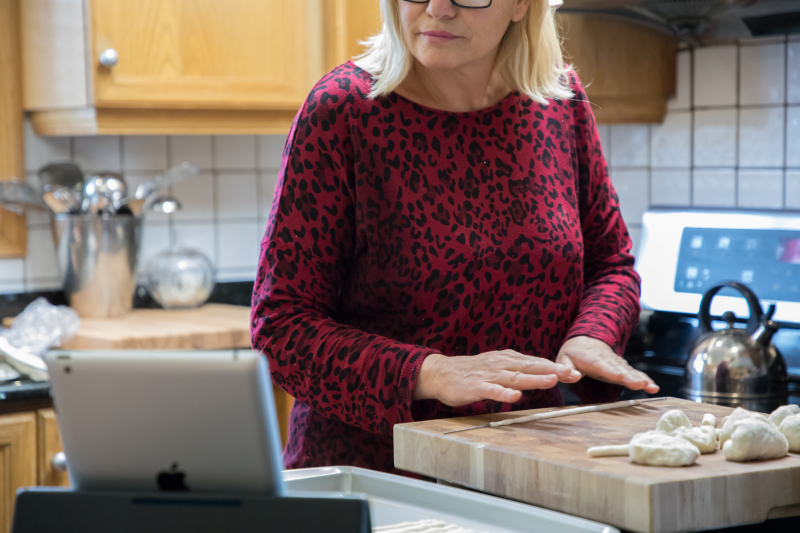 Woman rolling out dough while looking at a tablet
