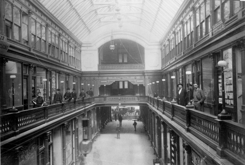 A black and white photograph of the Toronto Arcade. A boy and several men wearing hats stand around the railing on the second floor and look at the camera.