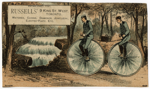 Full colour trade card with two men riding a bicycle with two large wheels and a lunch box sitting between them