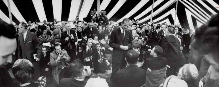 Large group of press behind Prince Philip in a tent talking to a man using a wheelchair