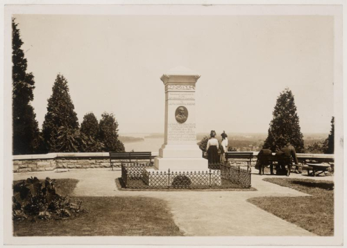 Vintage photo of monument with plaque on it and two bystanders nearby in surrounding garden
