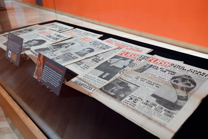 "A display case with multiple copies of tabloid newspaper ""Flash."""