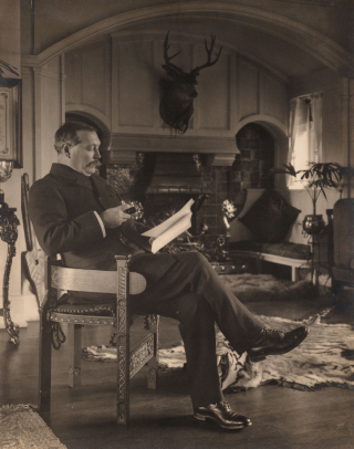 Arthur Conan Doyle is pictured reading and sitting in a chair. A fireplace is in the background.