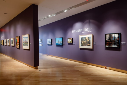 Interior image of the gallery with large framed paintings on the wall.