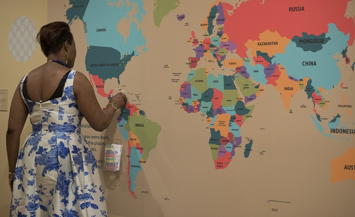 A woman in a floral dress places a small sticker on a large world map in the exhibit.