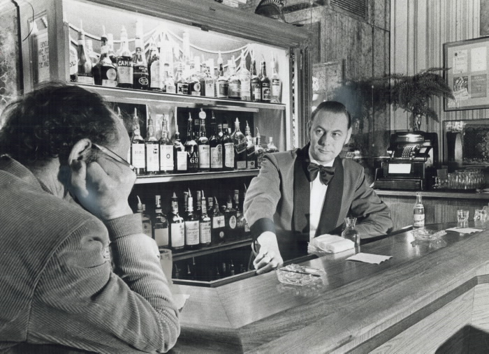 1975 Toronto Star Archives photograph showing Listening to a customer's problems is part of the day's work for barman Alfons Demleitner; who works at the Walker House Hotel