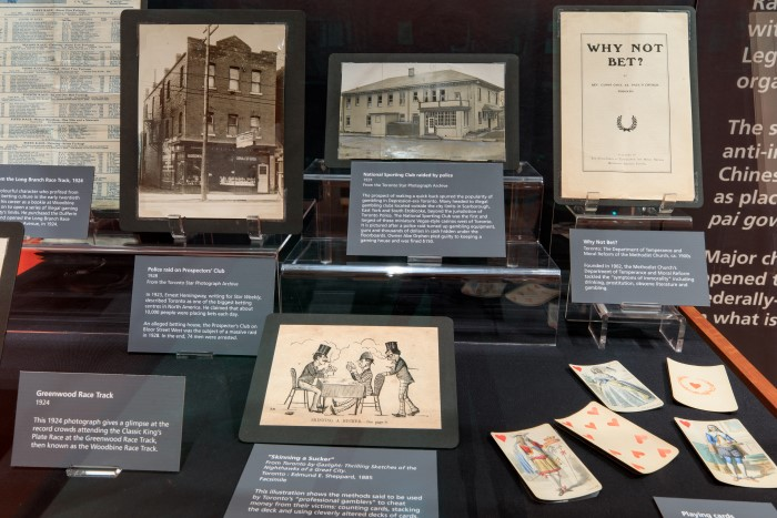 A display case with photographs and ephemera related to gambling in Toronto. Playing cards are displayed at right.