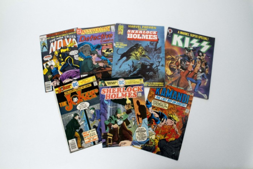 Covers of seven comic books are shown including a cover showing Sherlock Holmes meeting Batman, The Joker, and the band Kiss.