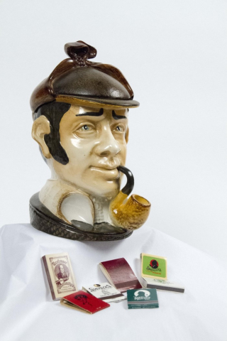 A ceramic humidor appears as a bust of Sherlock Holmes. Several matchbooks are displayed below.