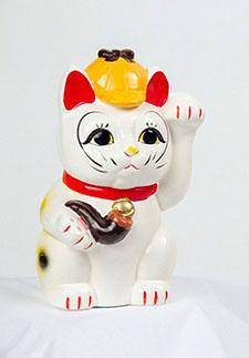 A white ceramic Maneki-neko cat wears a deerstalker hat and holds a pipe