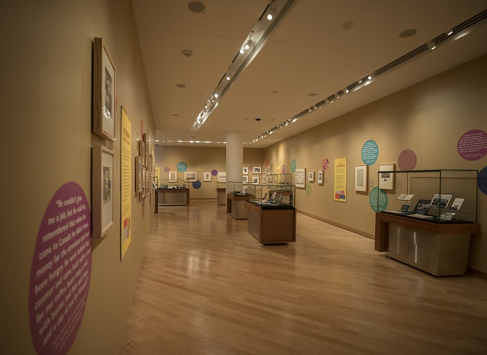 Gallery interior with glass display cases and framed photographs on wall. Walls are dotted with brightly coloured circles with patterns and personal quotes.
