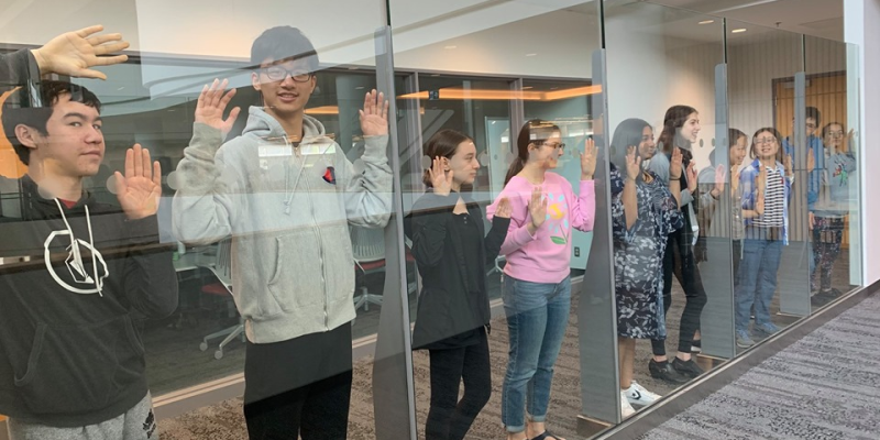 Teens pose through a glass wall-2019